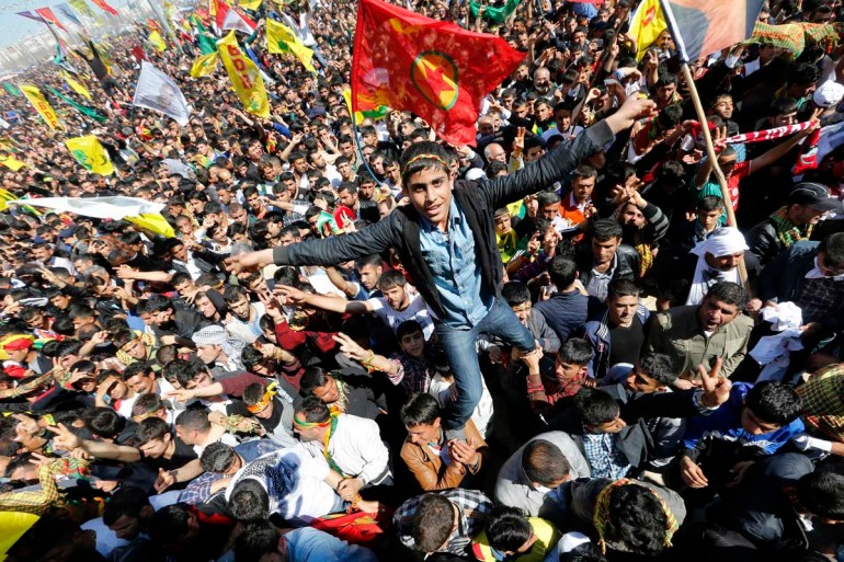 A youth gestures while being held up by others during a gathering celebrating Newroz, which marks the arrival of spring and the new year, in Diyarbakir